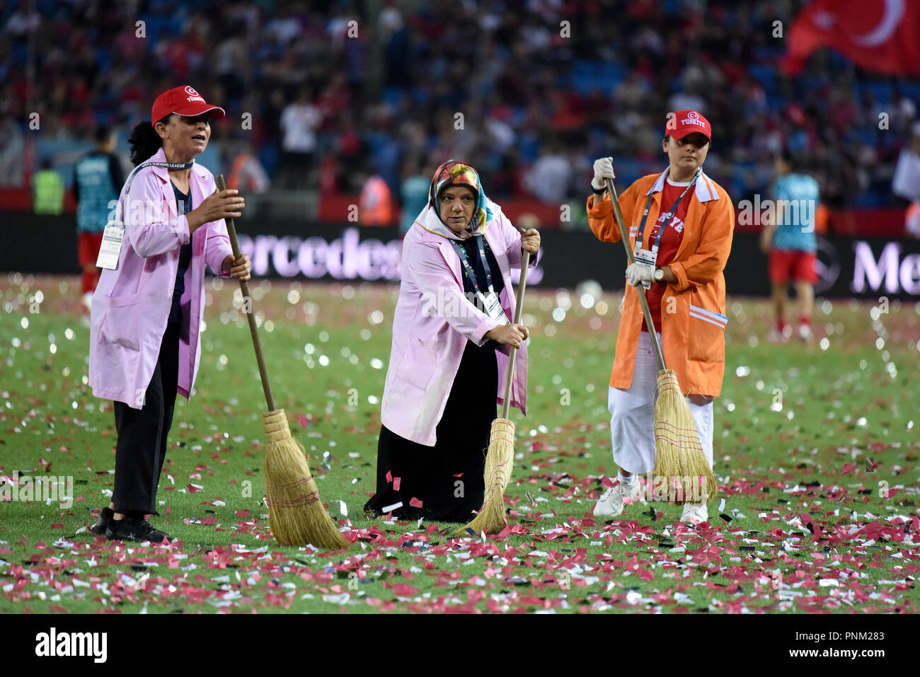Trabzon, Turkey - September 7, 2018. Female workers cleaning up confetti from pitch during half-time break in UEFA Nations League match Turkey vs Russ - Stock Image