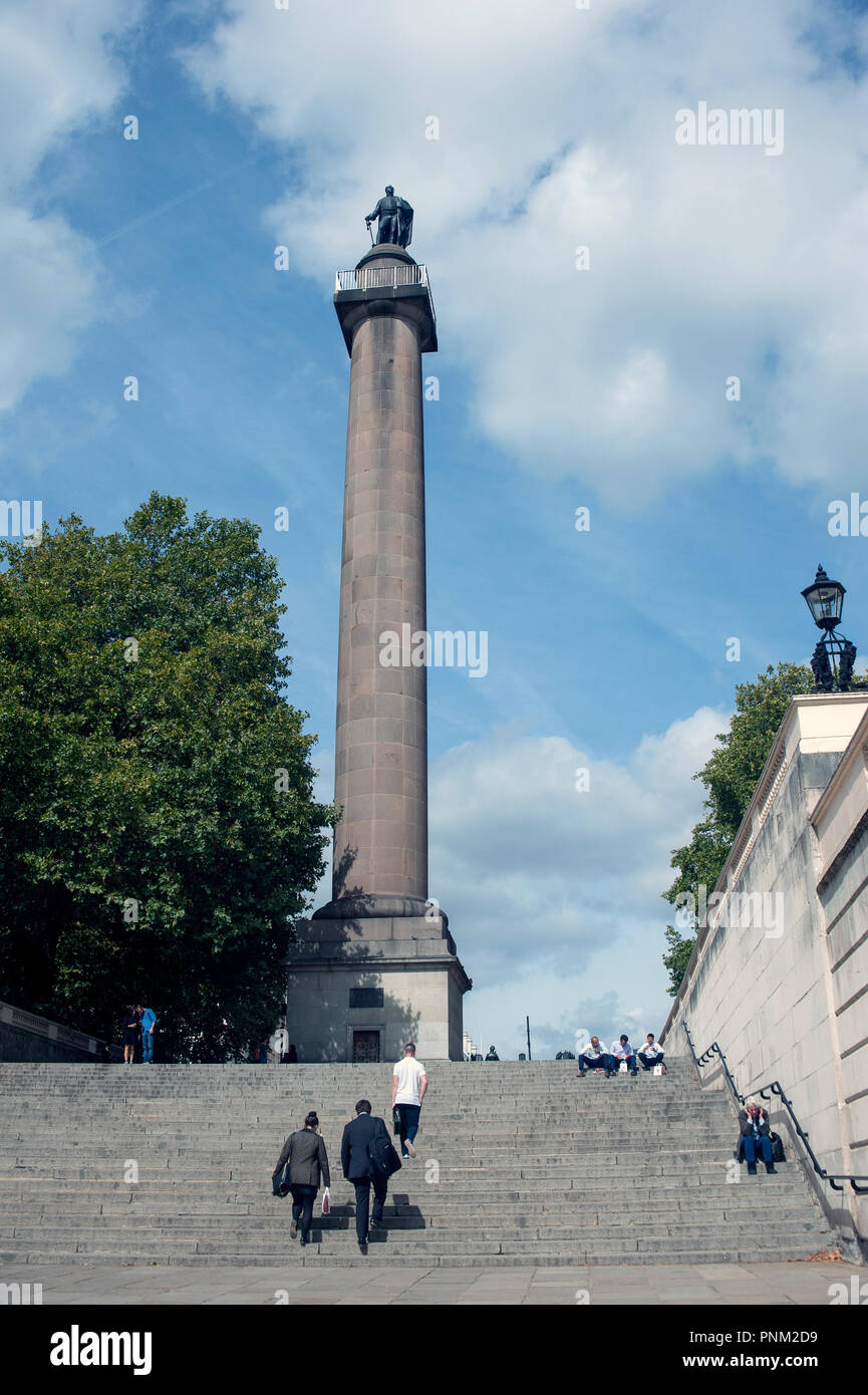 Duke of York Column at top of Duke of York steps, London, UK with several people walking up and sitting on steps. - Stock Image
