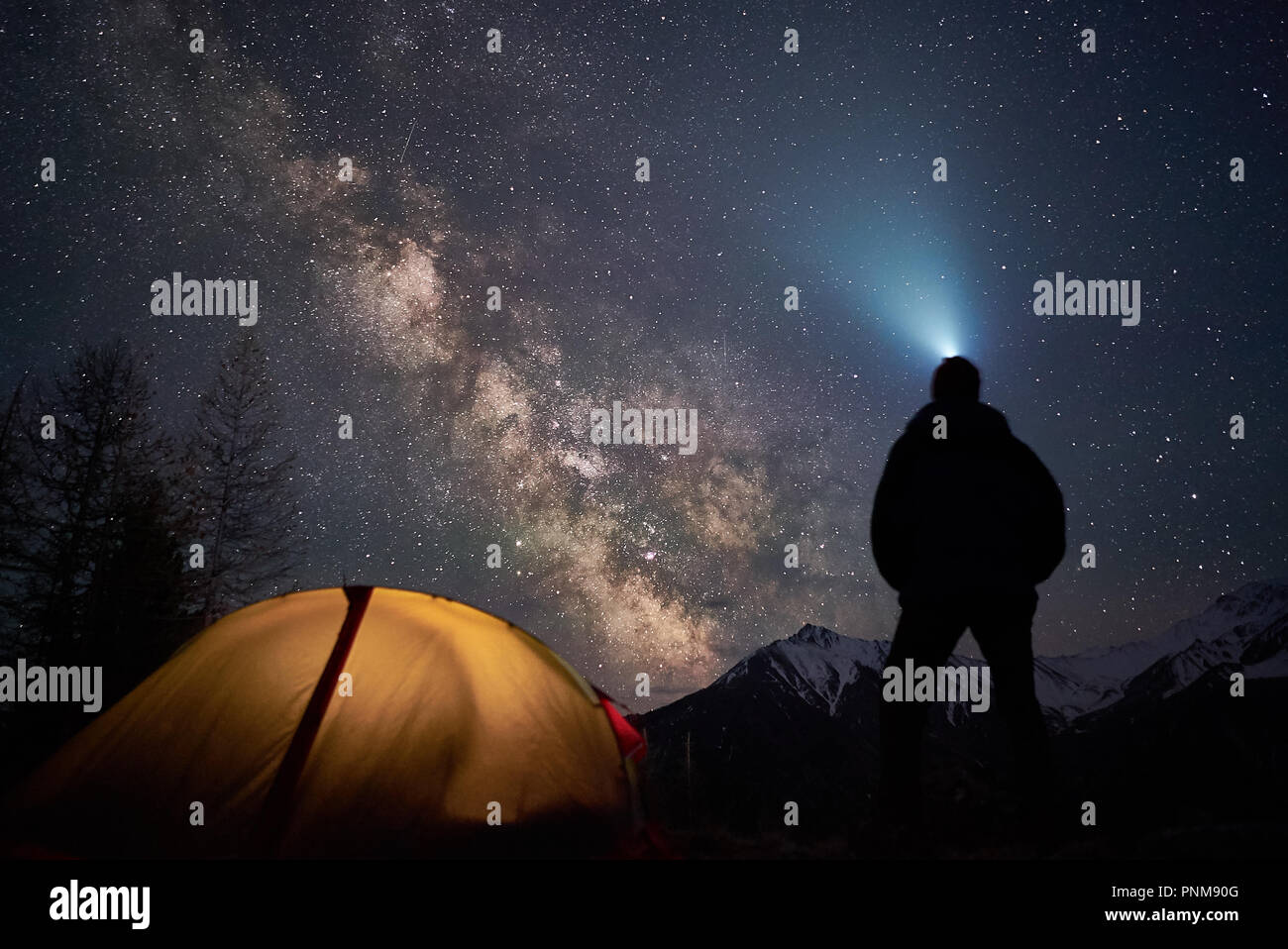 Man tourist with flashlight stands near his camp tent at night under a sky full of stars. - Stock Image
