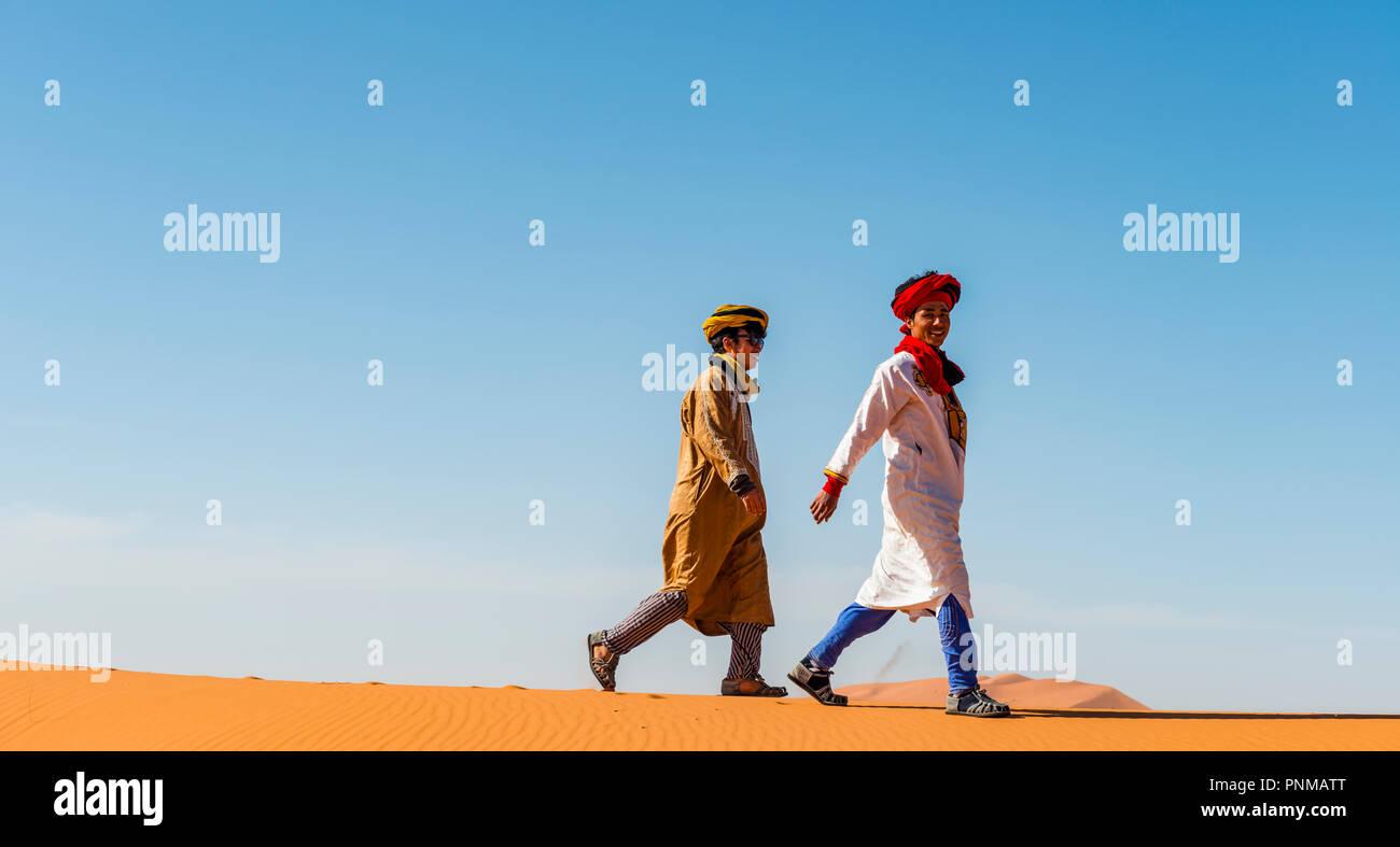 Two native Bedouins run on sand dune in the desert, Erg Chebbi, Merzouga, Sahara, Morocco - Stock Image