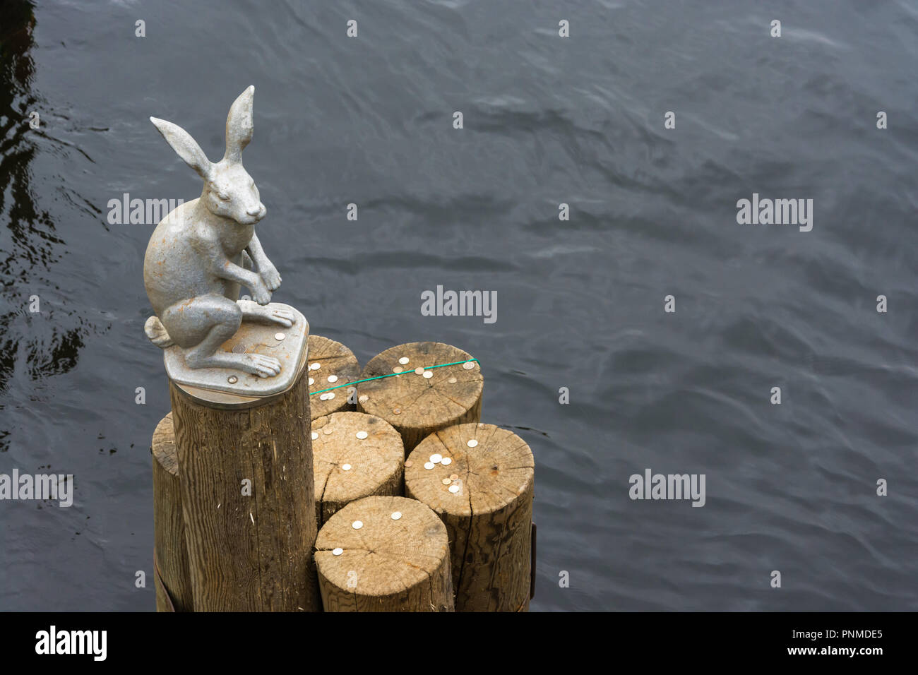 A little sculpture of a hare on the end of a log in the middle of the glistening water. - Stock Image