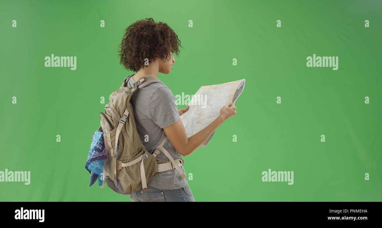 f650cb9543 Millennial girl reads a map while wearing her hiking backpack on green  screen