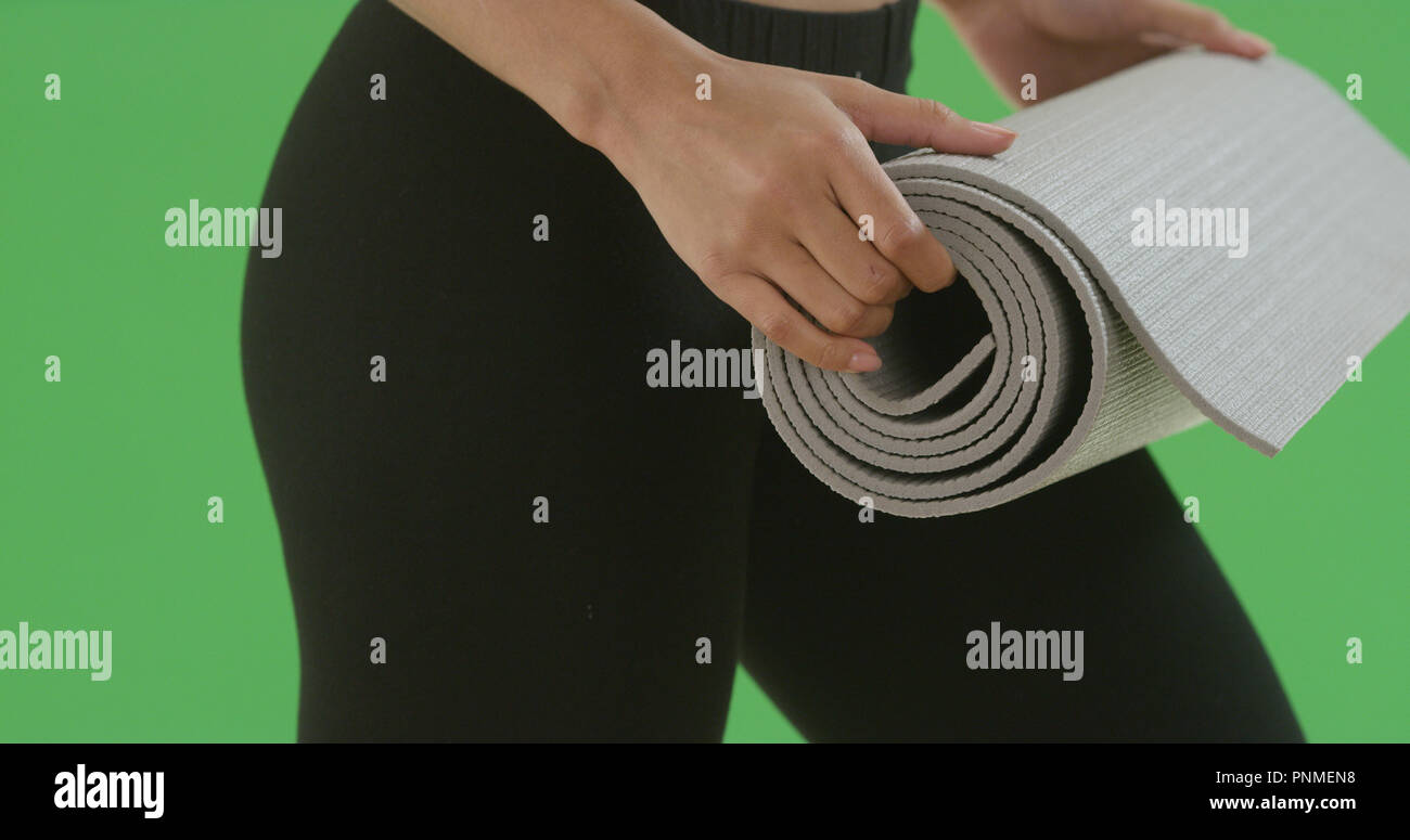 Close-up of black girl in yoga pants ready to roll out yoga mat on green screen - Stock Image