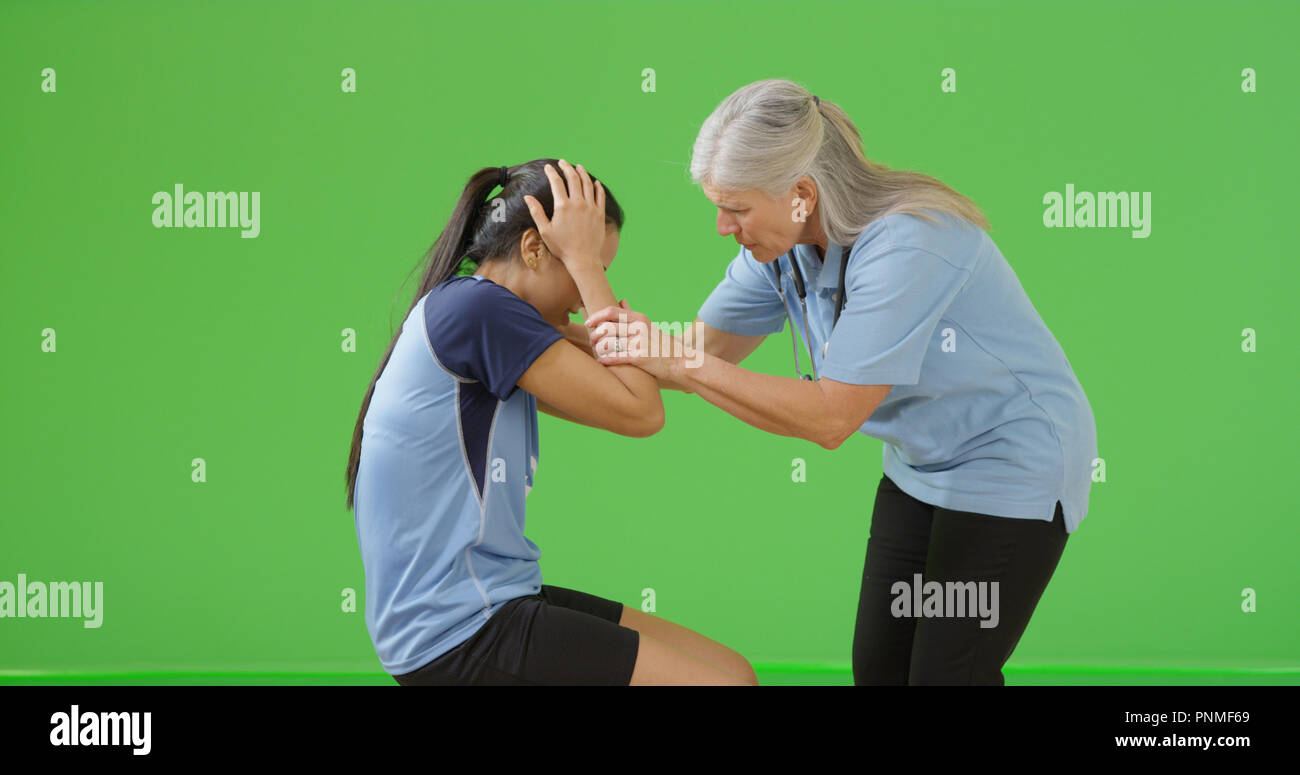 Old female paramedic examining soccer player's injury on green screen - Stock Image