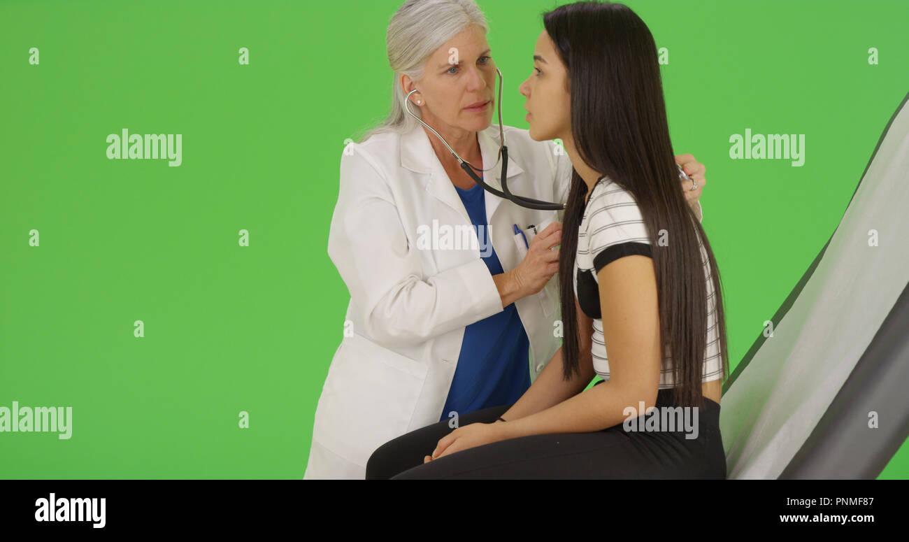 A young teen girl receives a medical examination on green screen