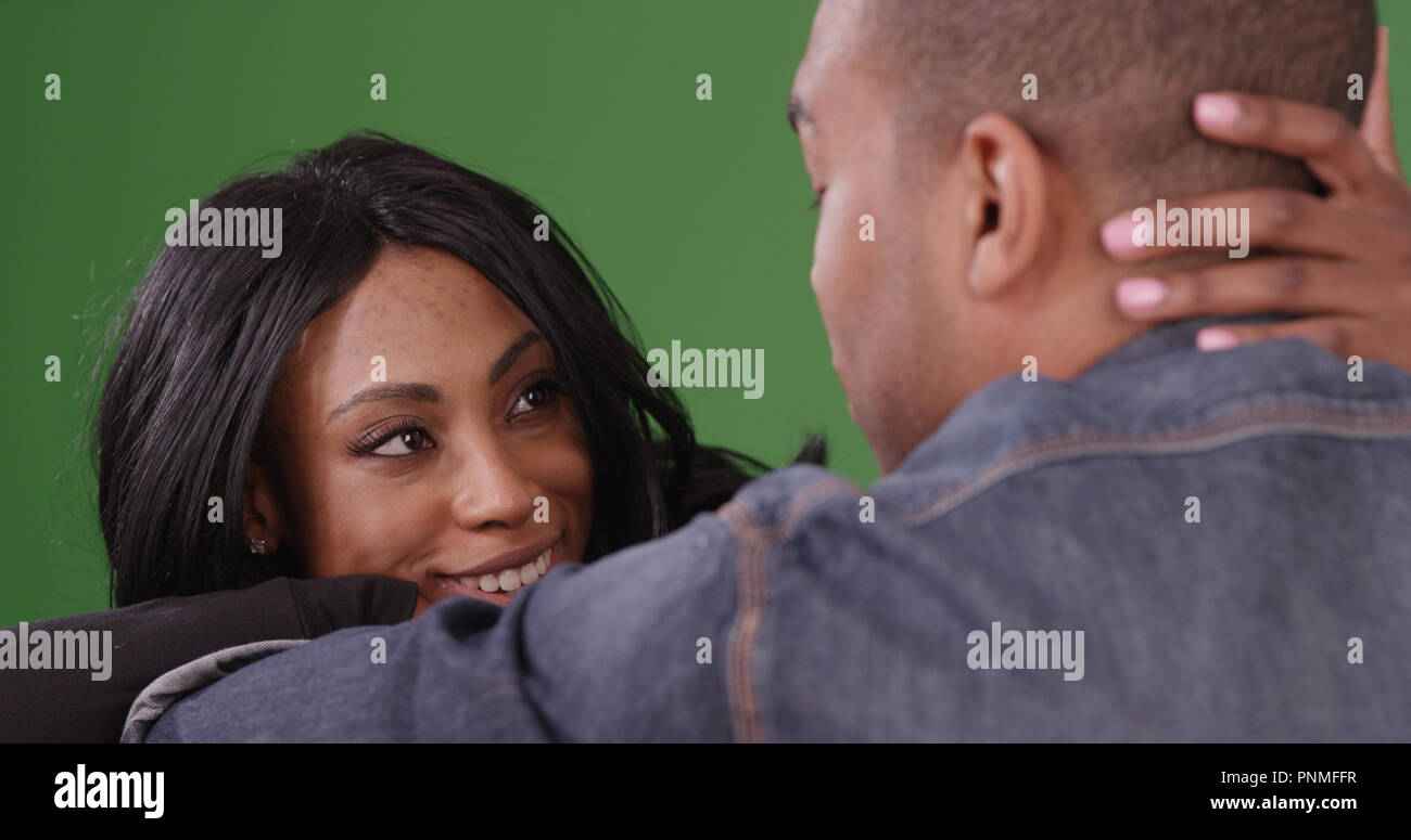Intimate couple sitting together looking into each others eyes on green screen - Stock Image