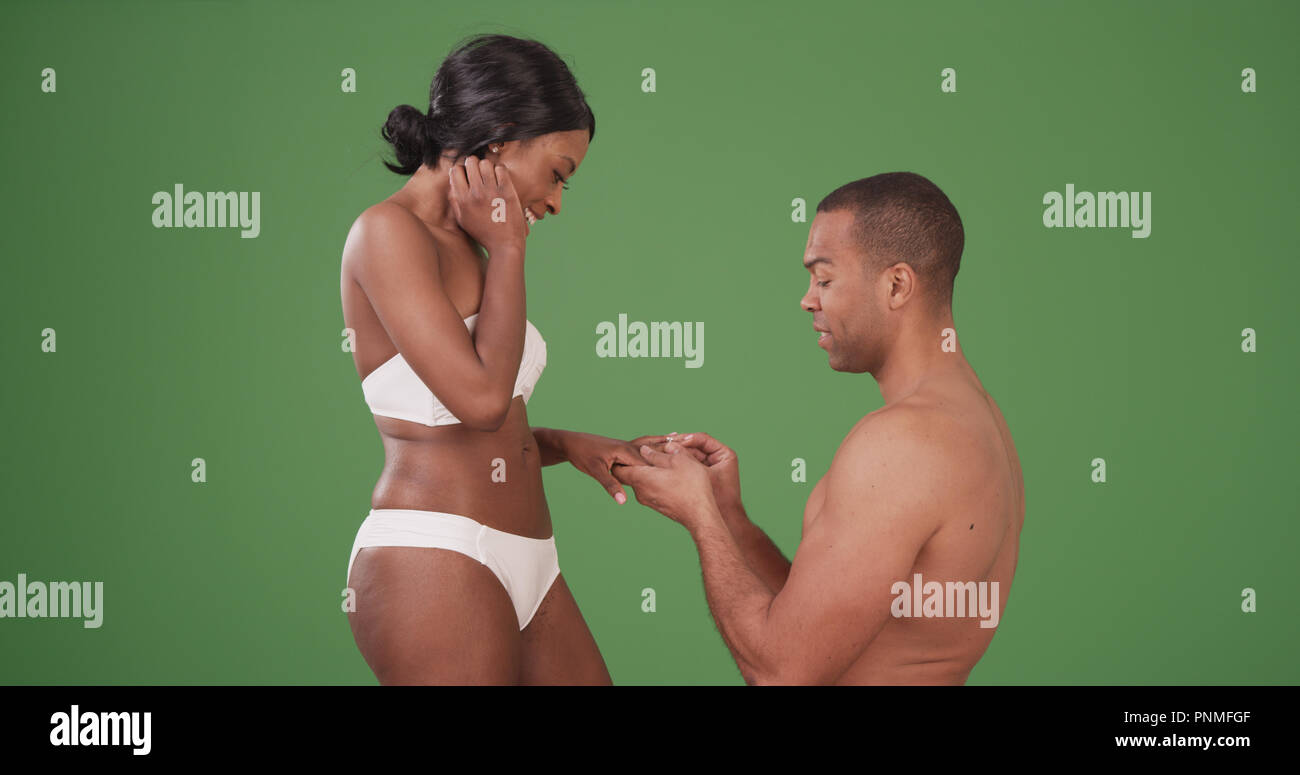 Man proposing to fiancee in their swimwear on green screen - Stock Image