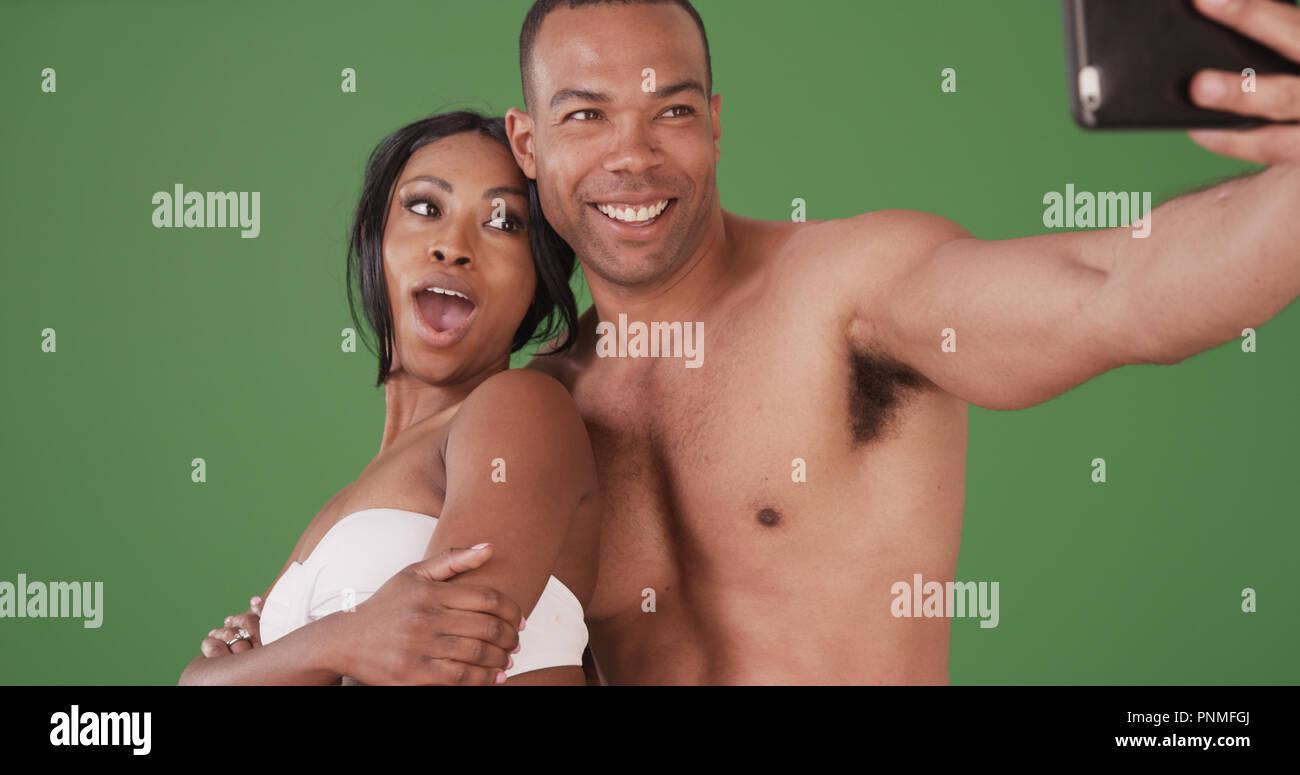 Black couple in swimwear taking selfie on green screen - Stock Image