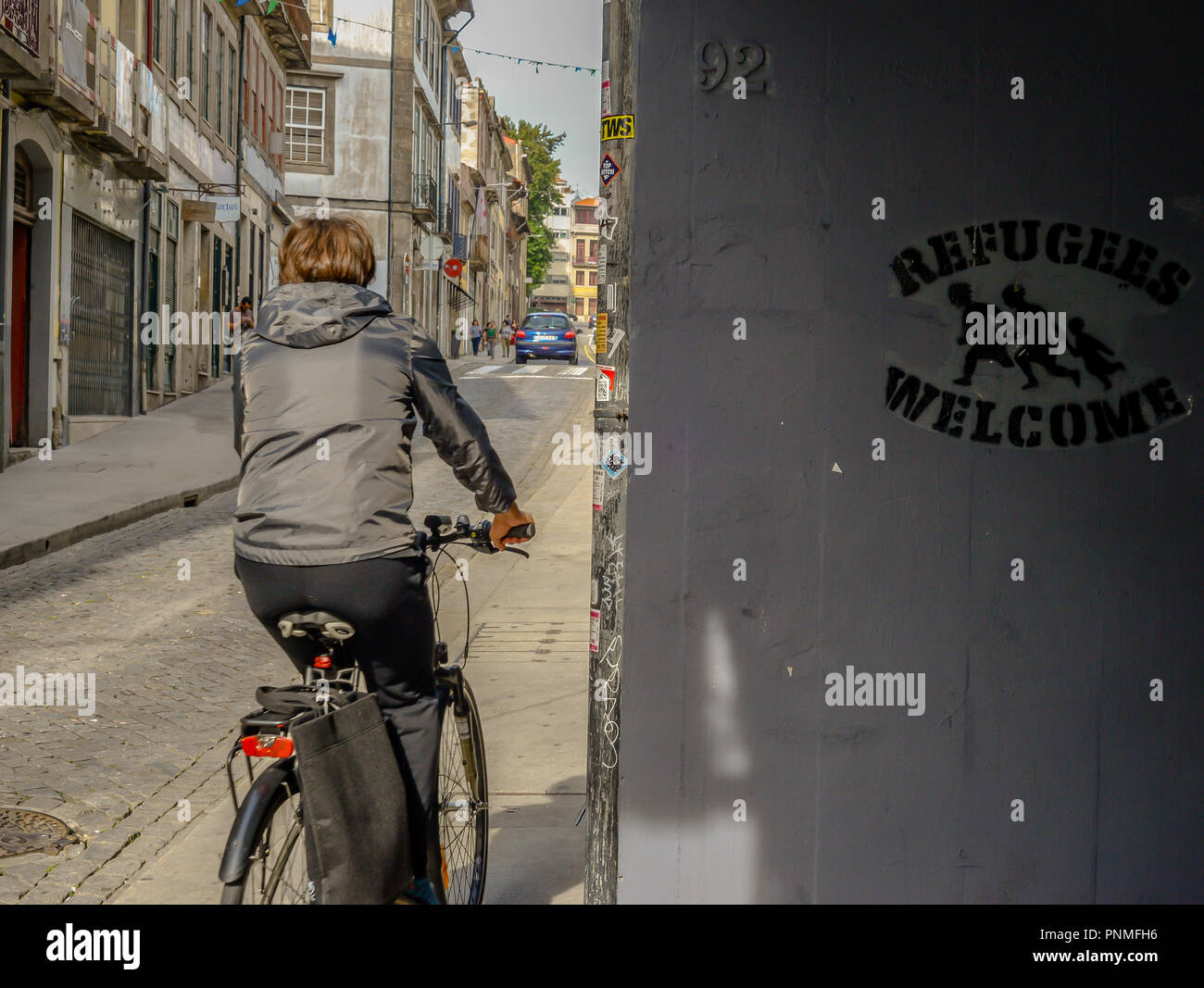 A woman riding past a political message - Spain - Stock Image