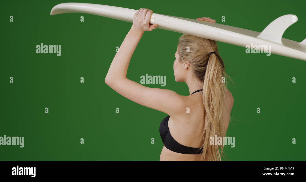 Pretty white girl with surfboard ready to catch some waves on green screen - Stock Image