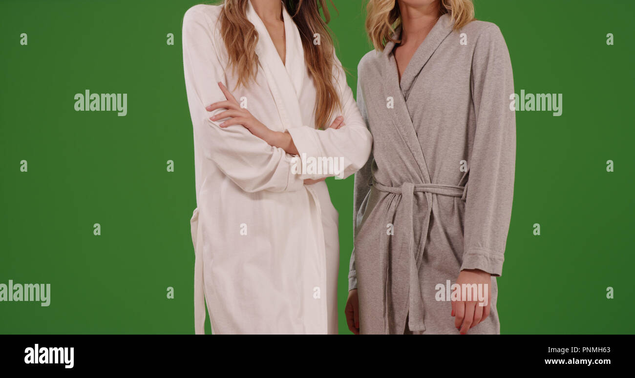 Couple of female models wearing bath robes on green screen - Stock Image