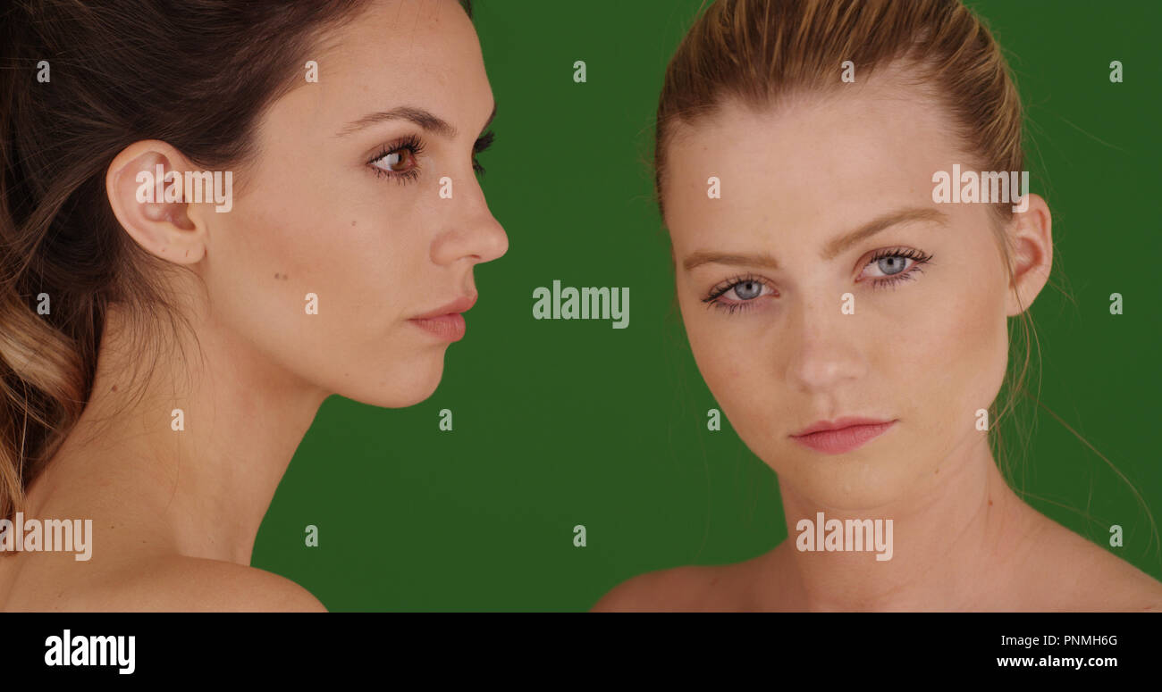 Portrait of a pair of lovely white women wearing makeup of green screen - Stock Image