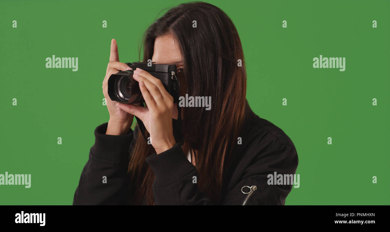 Female photographer taking picture with dslr camera on green