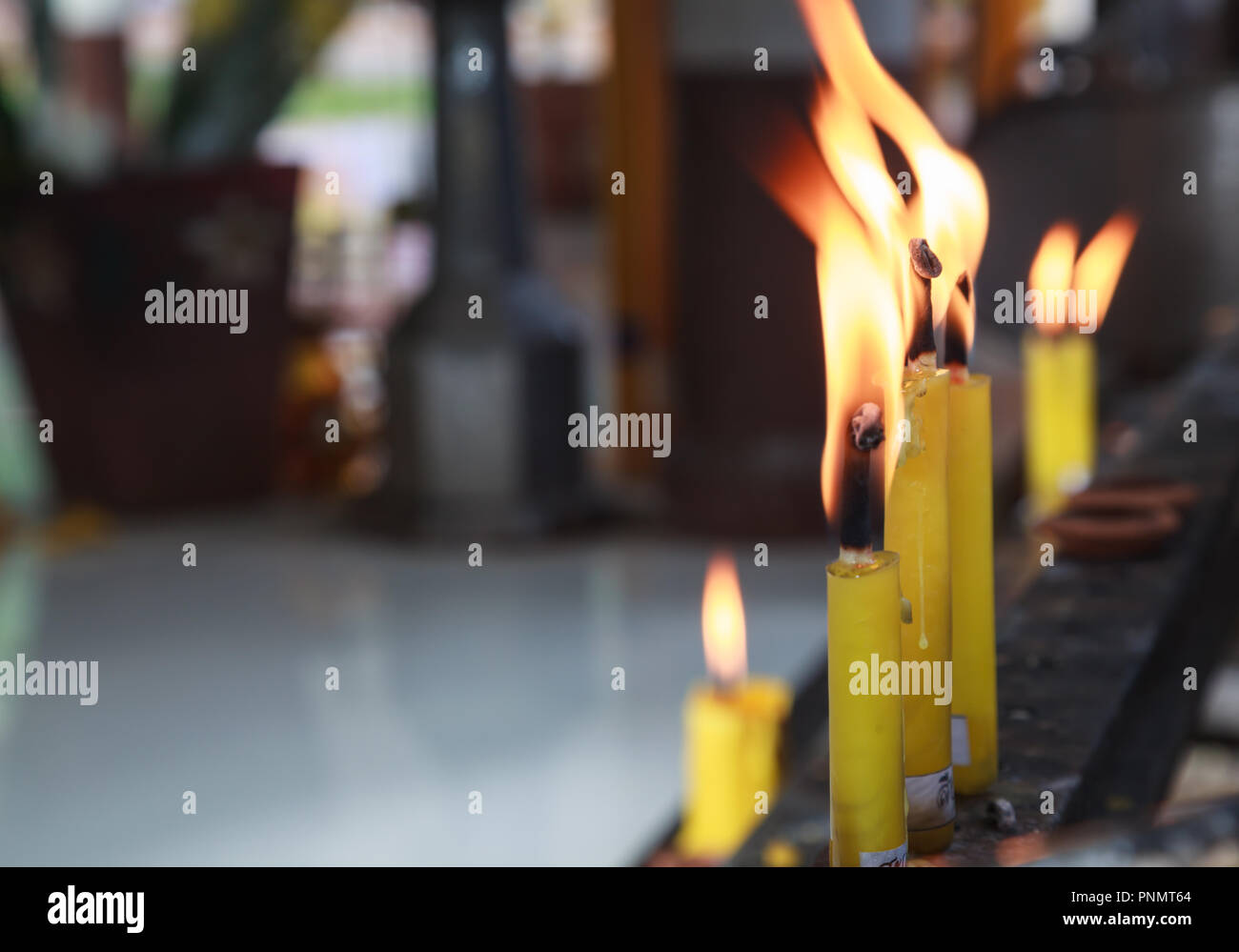 Yellow Candlesticks lit on the prayer shelf in Buddhist Temple Shrine. Buddhism, Asian traditional religious ceremony, Rituals, Making a wish, Meditat - Stock Image