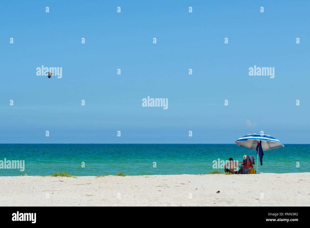 Couple under an colourful beach umbrella enjoying a day out on the beach of Chuburna, Yucatan, Mexico. Turquoise waters, calm sea. white sand. - Stock Image