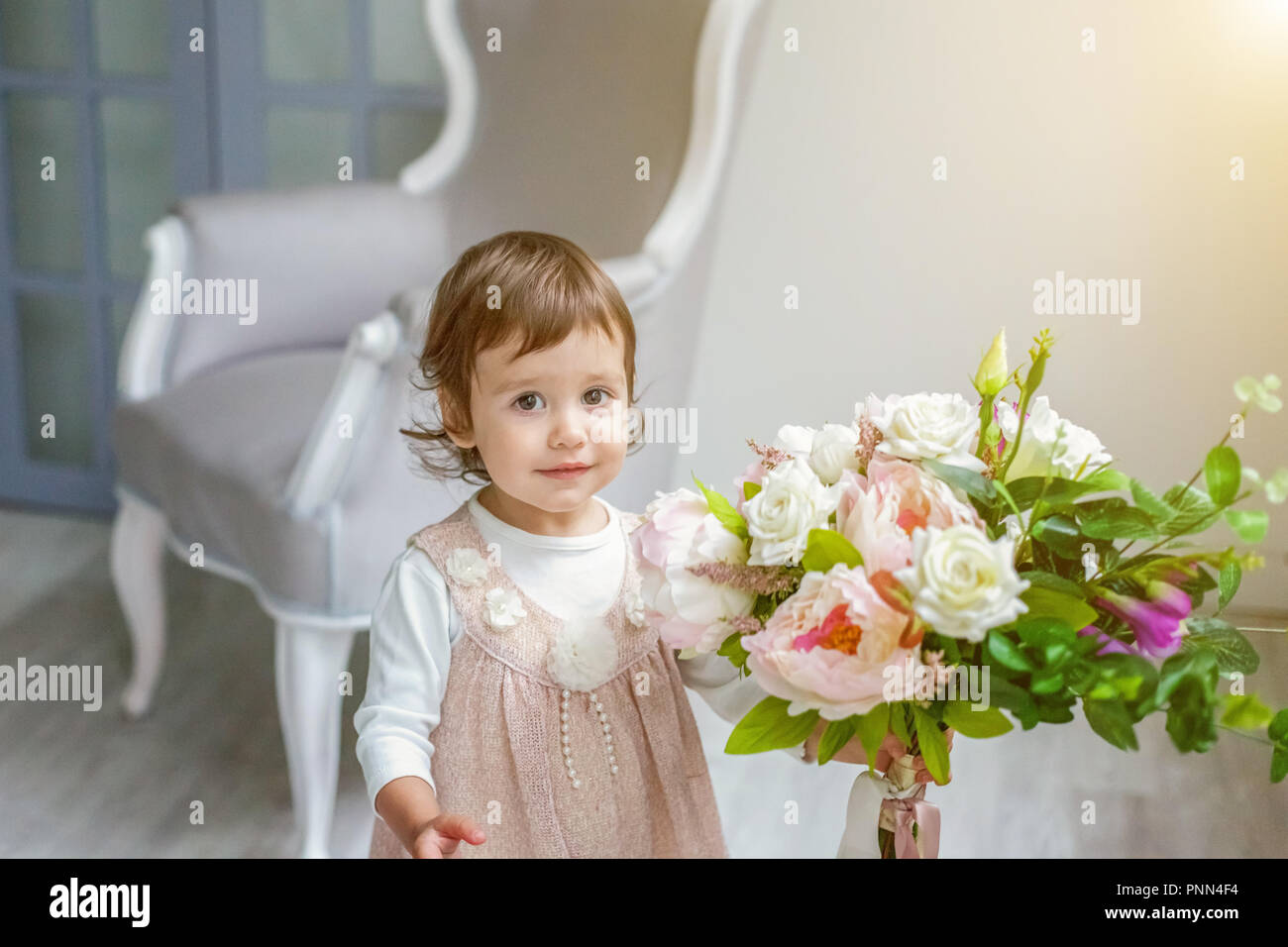 a2cc57212f75 Sweet little girl in pastel pink dress at home play with flowers ...