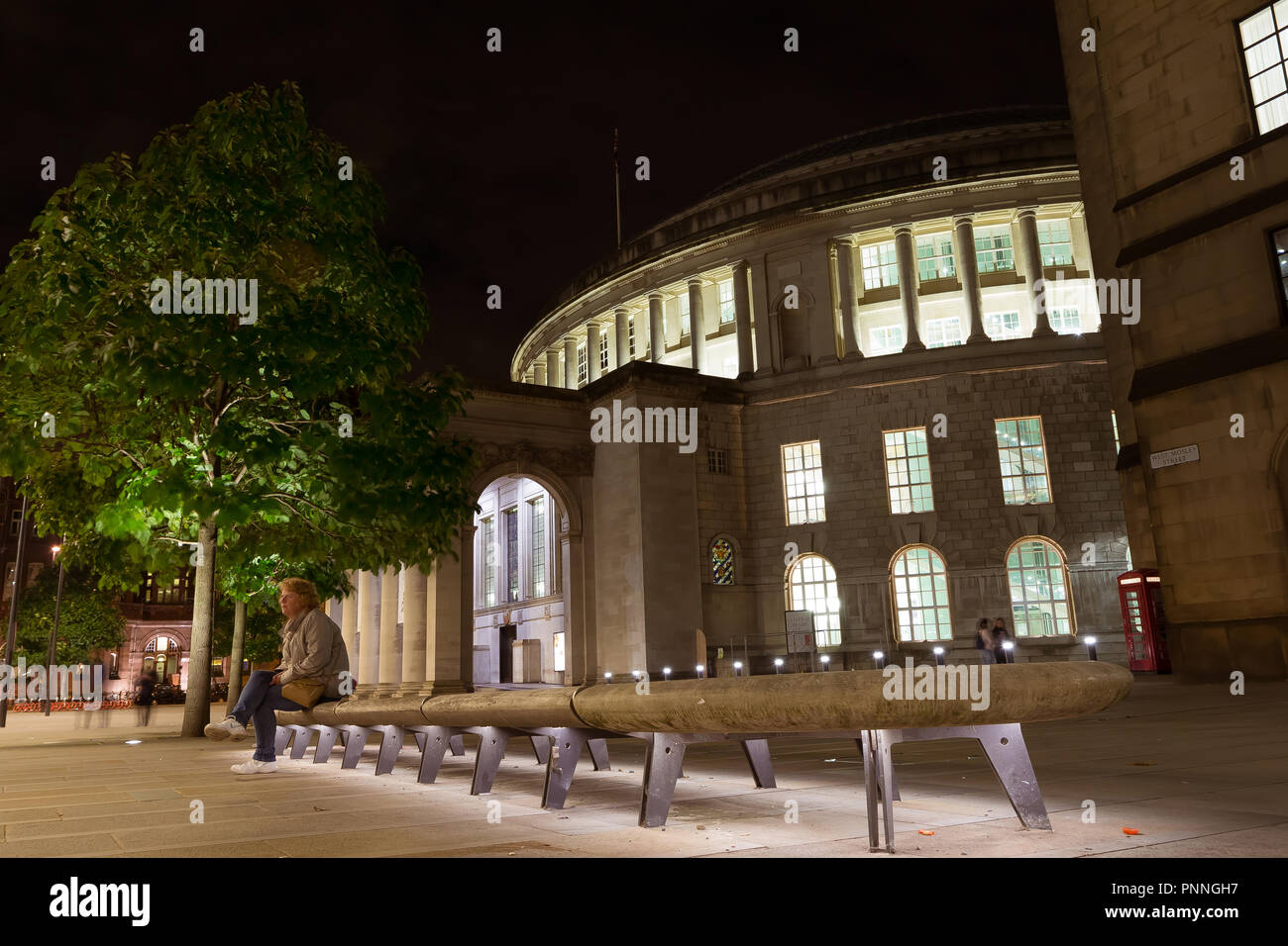 September 2017 - a woman sits at night on an illuminated stone bench in front of Manchester Central Library, the iconic building in the center of Manc - Stock Image