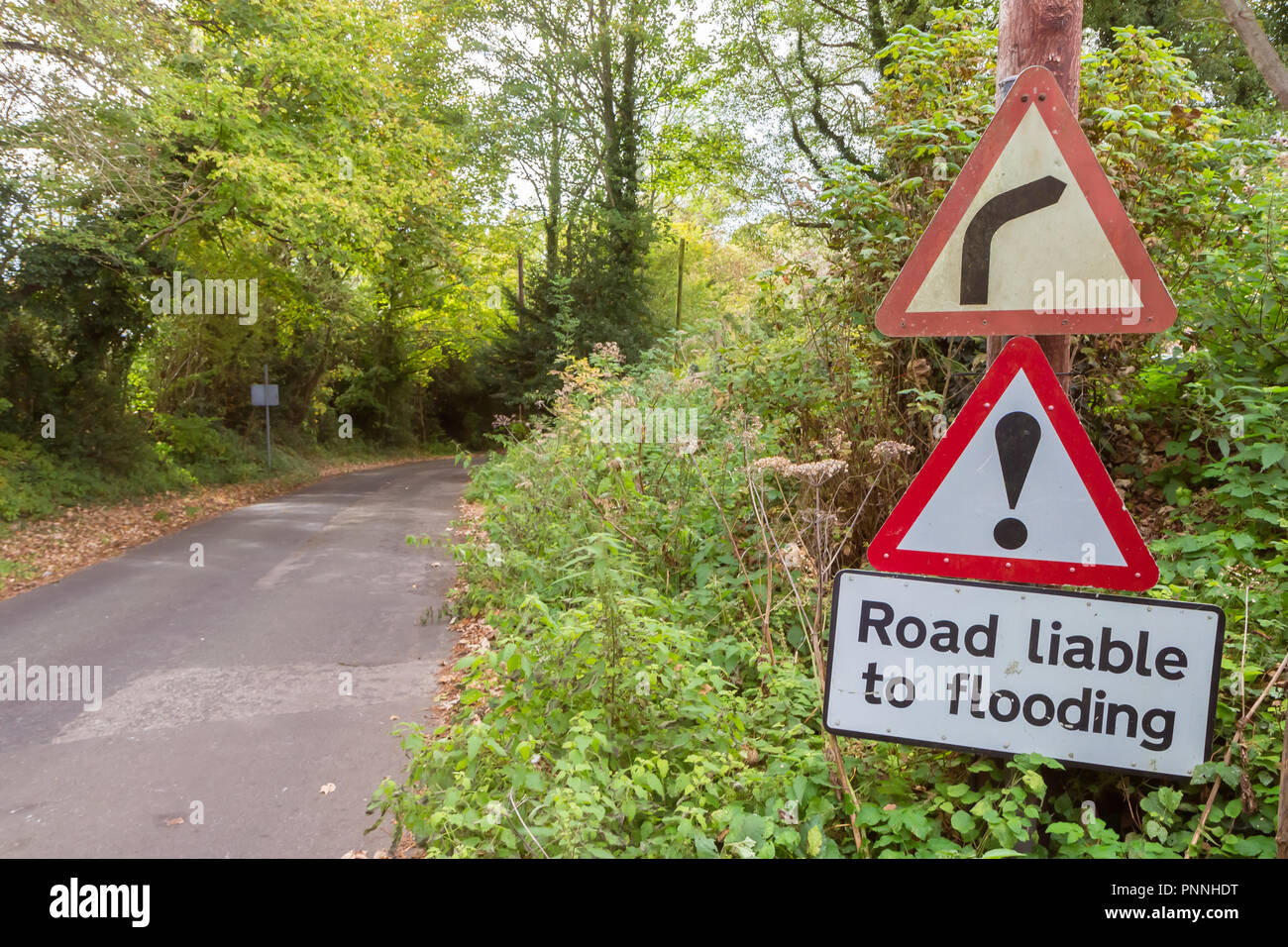 Flood warning sign on country road in England, UK - Stock Image