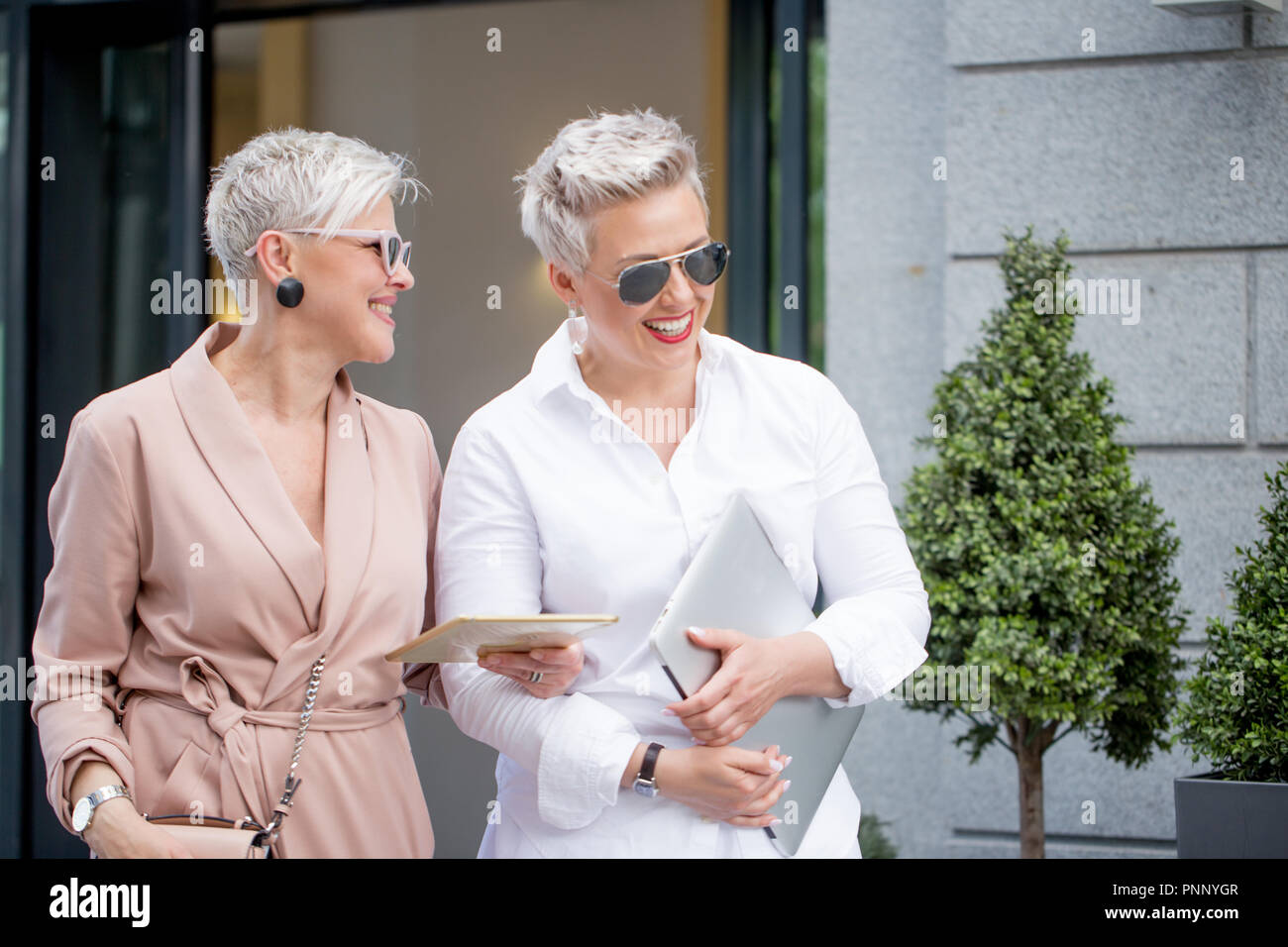 Two businesswoman walking on street near building. business woman going together with tablet computer - Stock Image