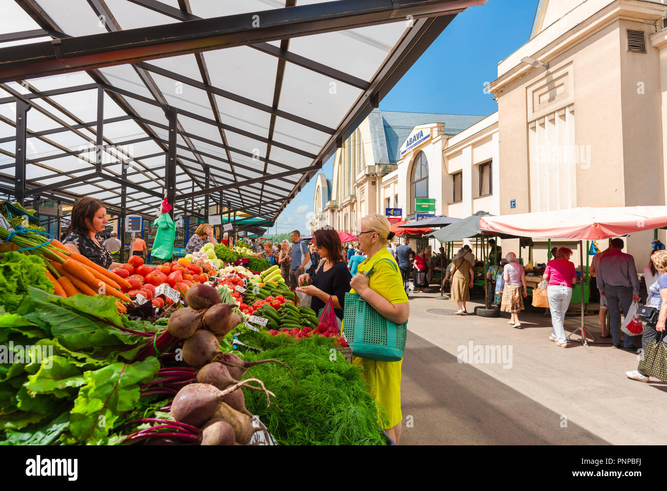 Riga Central Market, view of Latvian women buying vegetables at a stall outside the Riga Central Market building, Latvia. - Stock Image