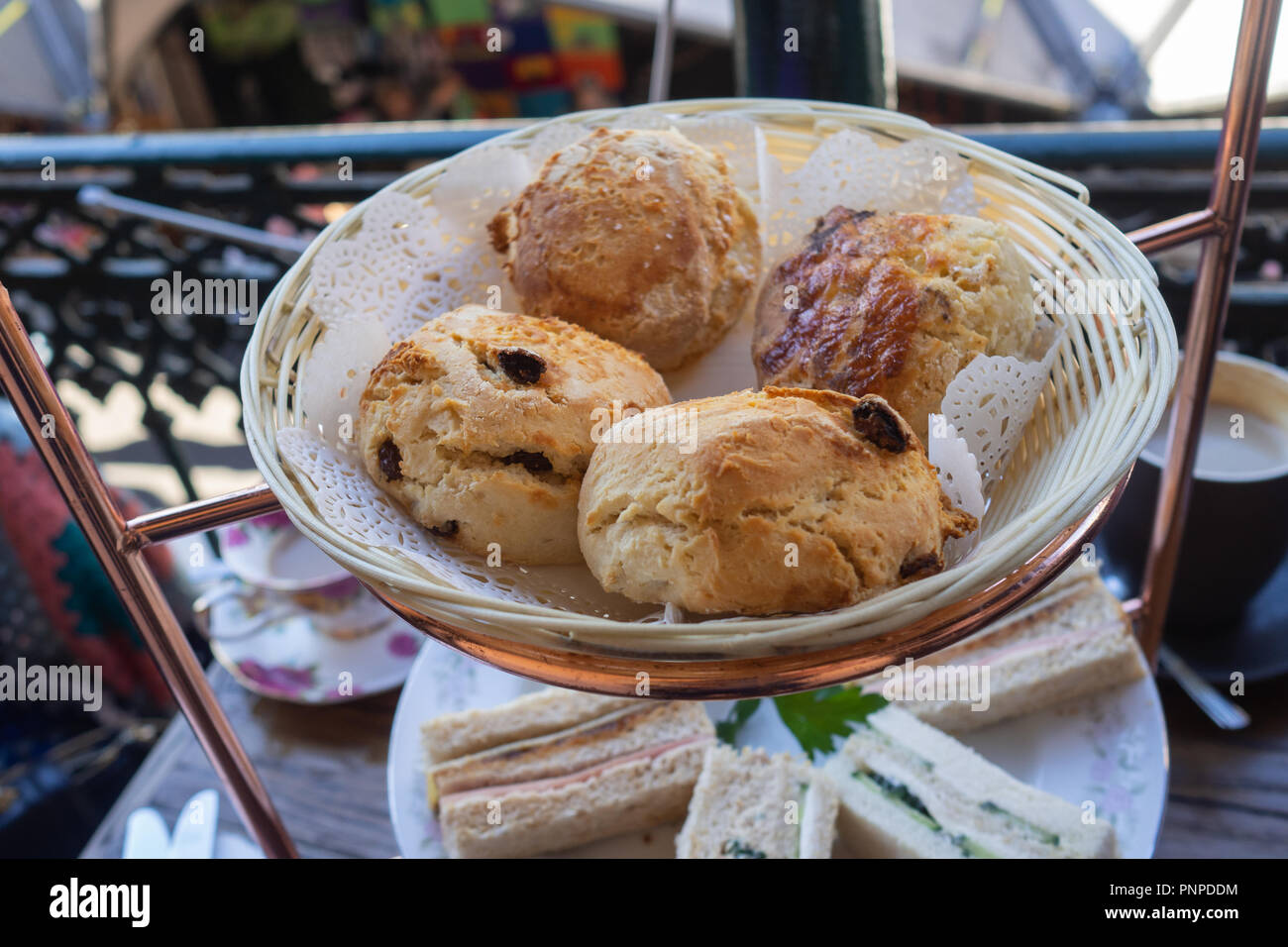 Freshly baked scones in a basket at high tea - Stock Image
