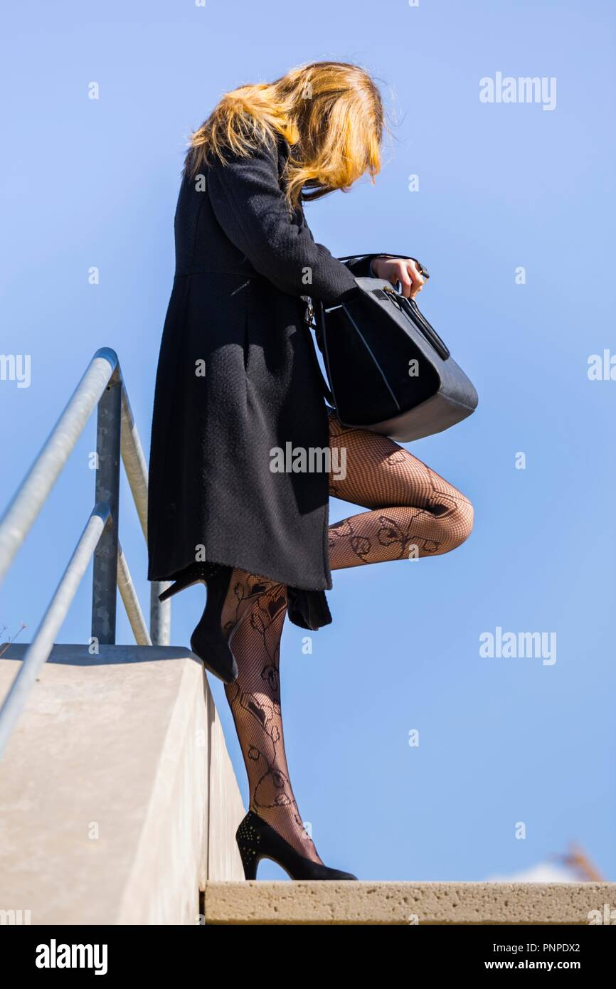Teenager girl standing on street looking for something in her handbag profile Black tights MR slim thin stilettos shoes Stock Photo
