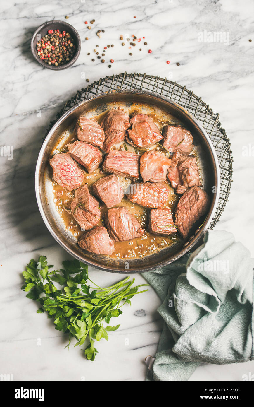 Braised beef meat stew with fresh parsley in cooking pan - Stock Image