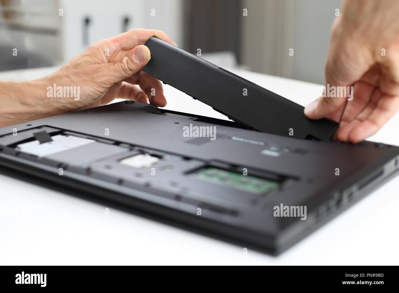 A Battery  exchange of a notebook or laptop by y professional - Stock Image