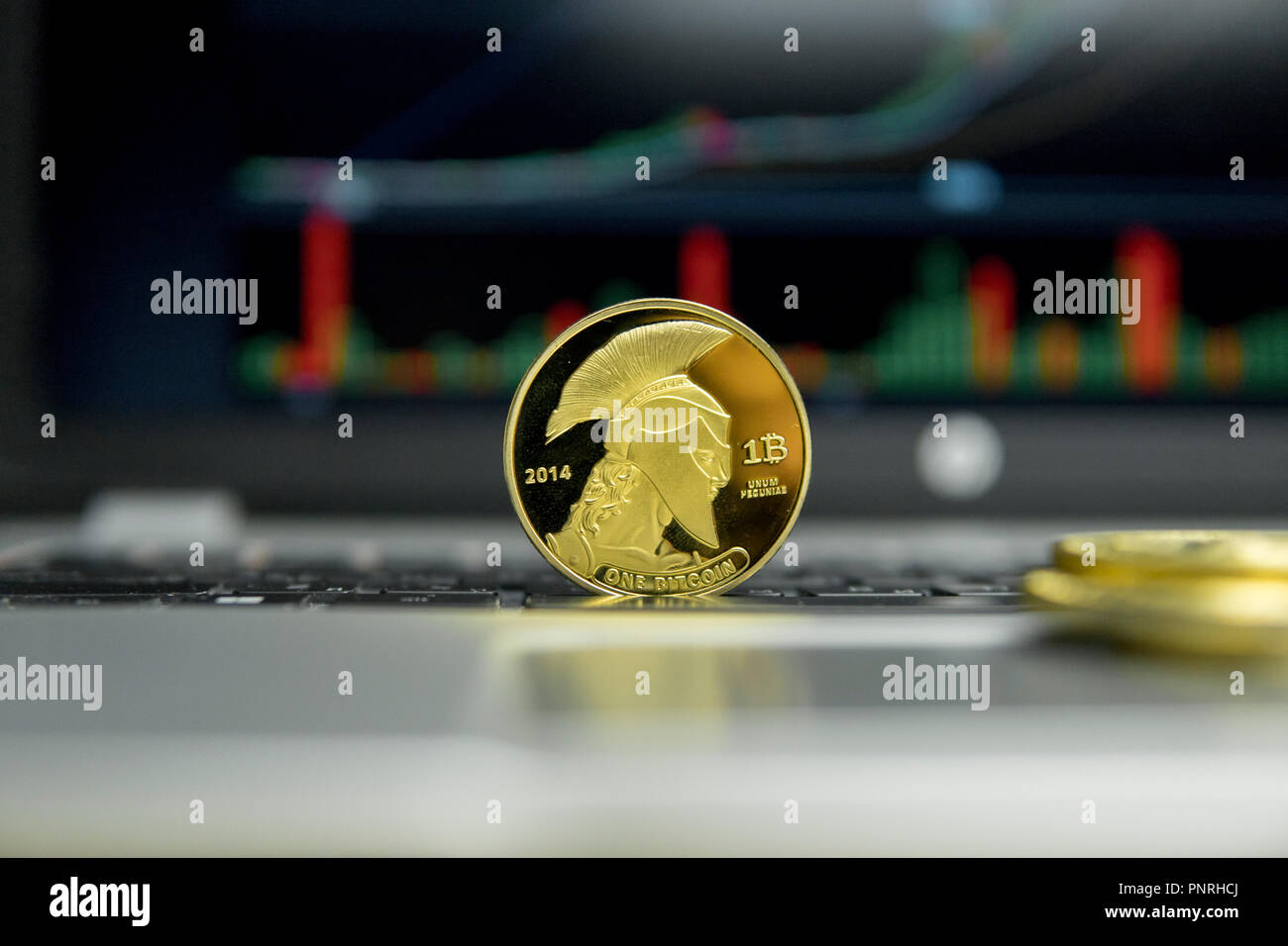 Golden titan bitcoin coin with gold coins lying around on a silver keyboard of laptop and diagram chart graph on a screen as a background. Mining of bitcoins online bussiness. Titans trading. Stock Photo