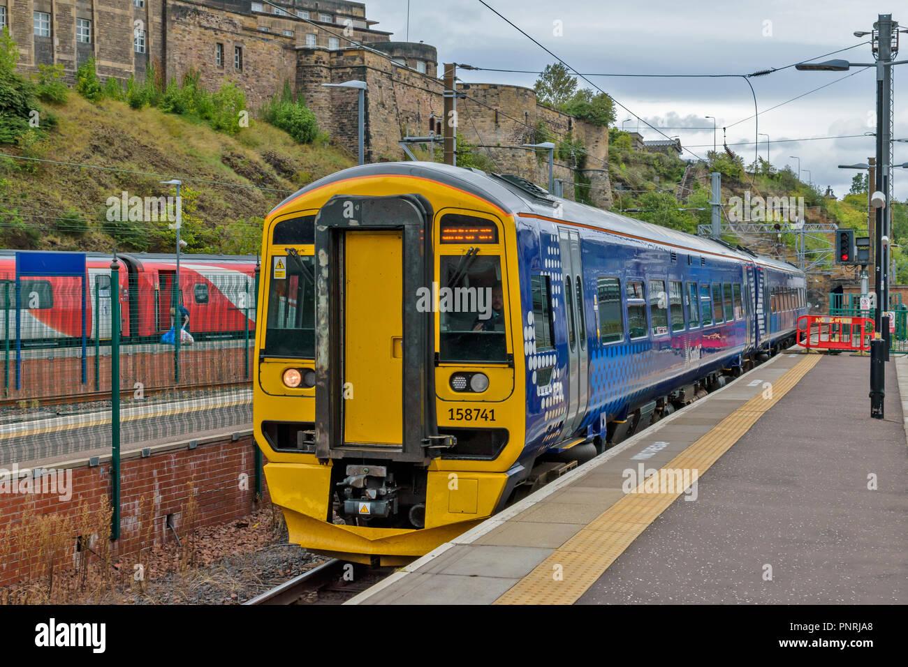 EDINBURGH SCOTLAND WAVERLEY STATION BLUE CARRIAGES OF SCOT RAIL TRAIN ARRIVING AT PLATFORM - Stock Image