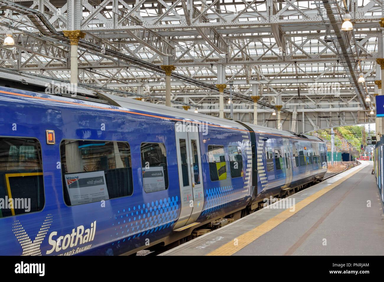 EDINBURGH SCOTLAND WAVERLEY STATION BLUE CARRIAGES OF SCOT RAIL TRAIN WAITING AT PLATFORM - Stock Image