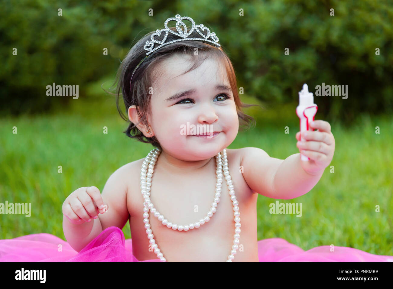 Baby toddler girl first birthday anniversary party, playing with candle, dirty face and making a mess of pink cake with candle. Princess costume - Stock Image