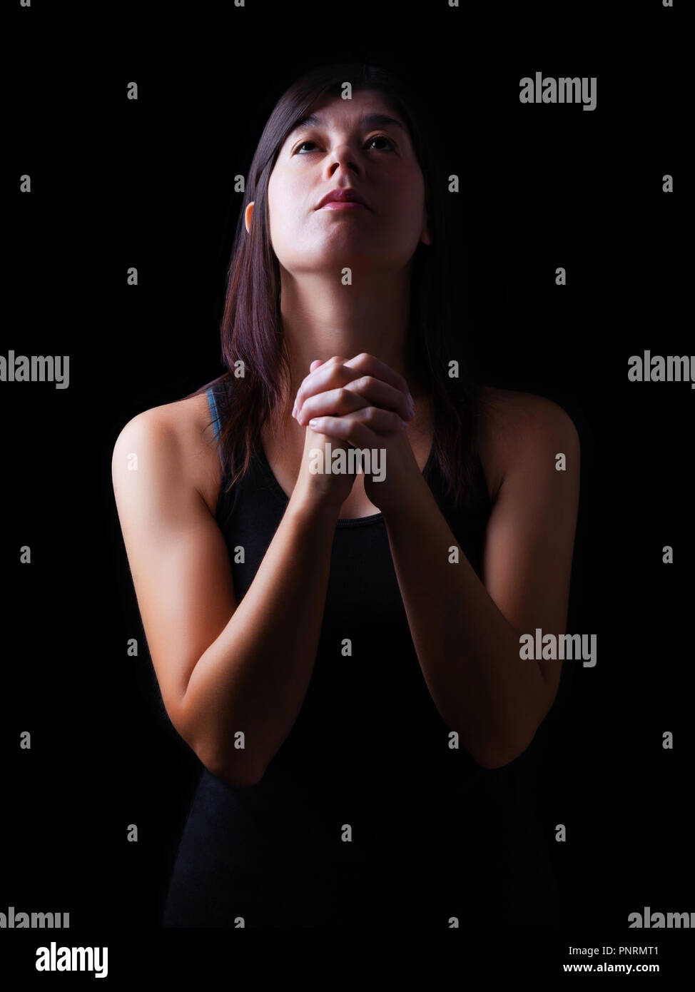 Faithful woman praying, hands folded in worship to god with looking up in religious fervor, on a black background. Concept for religion, faith, prayer - Stock Image