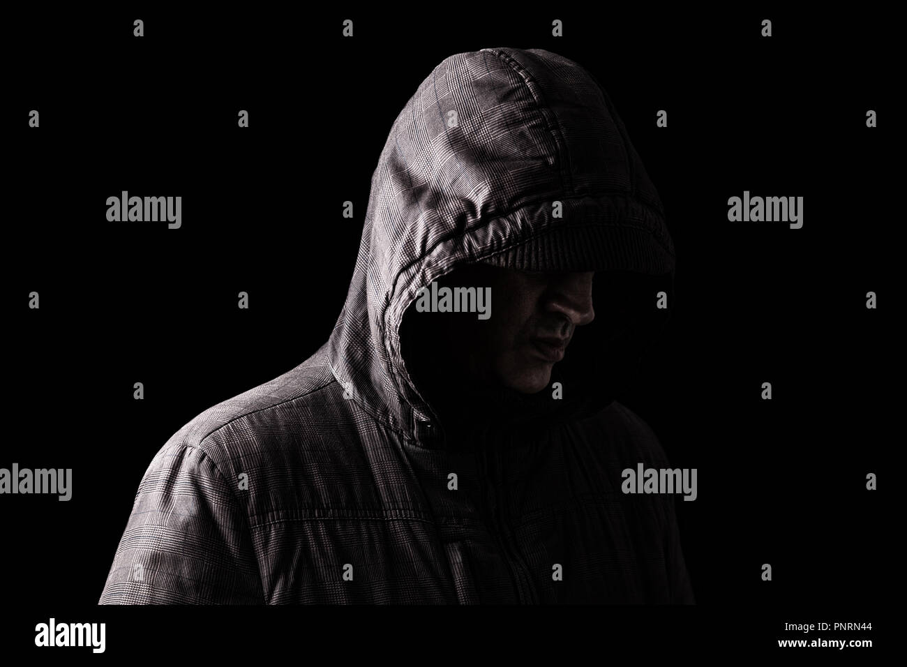 Lonely, depressed and fragile Caucasian or white man hiding face, standing in the darkness. Low key, black background. Concept for loneliness, depress - Stock Image