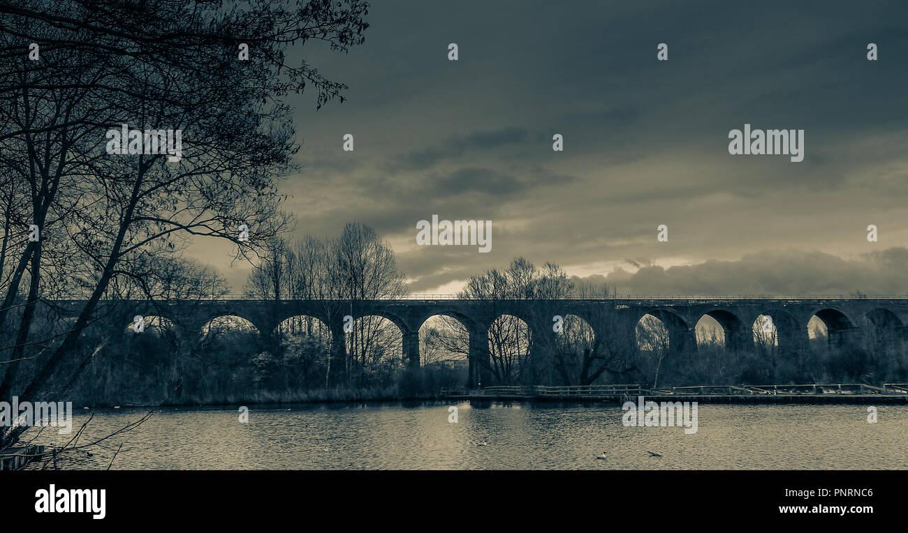 Railway viaduct and lake, Reddish Vale country park, Stockport, Cheshire, UK. - Stock Image