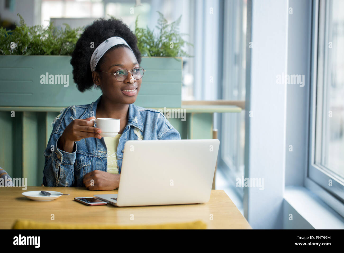 African female blogger, typing a new post during lunchtime at a cafe. - Stock Image