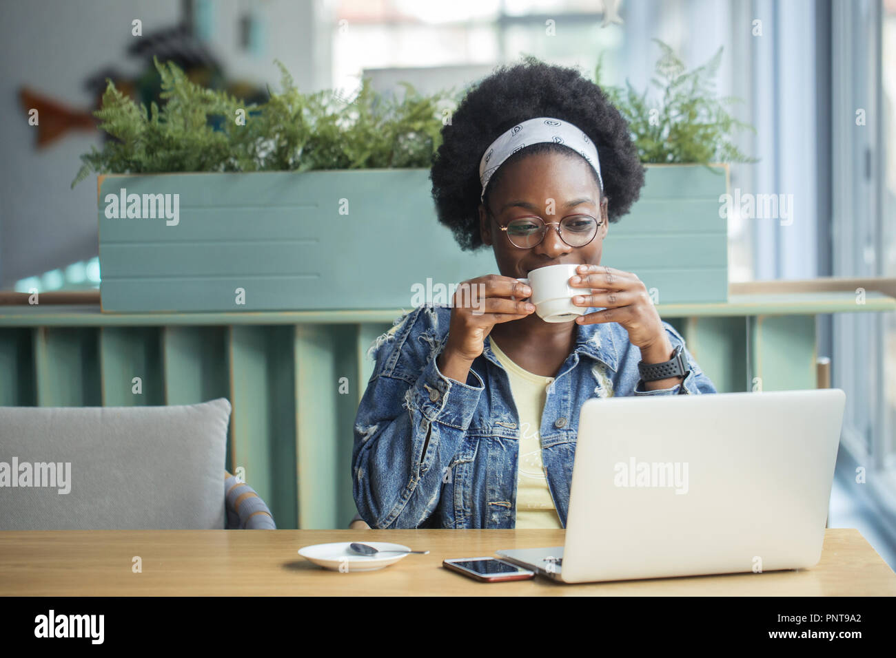 African female blogger, typing a new post during lunchtime at a cafe. Stock Photo