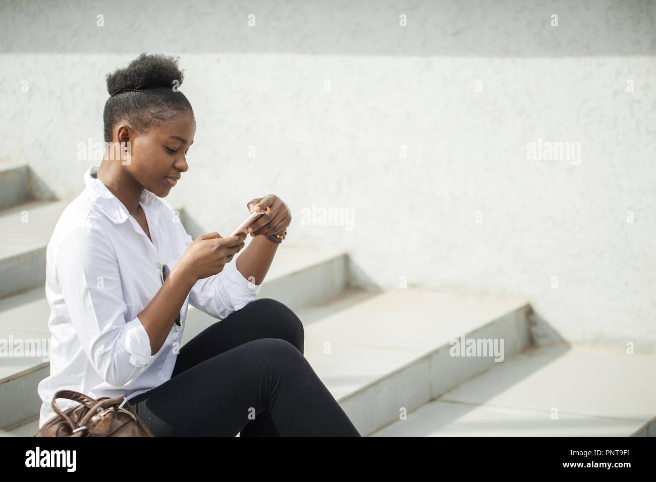 African woman using smart phone while sitting on white stairs outdoors. - Stock Image