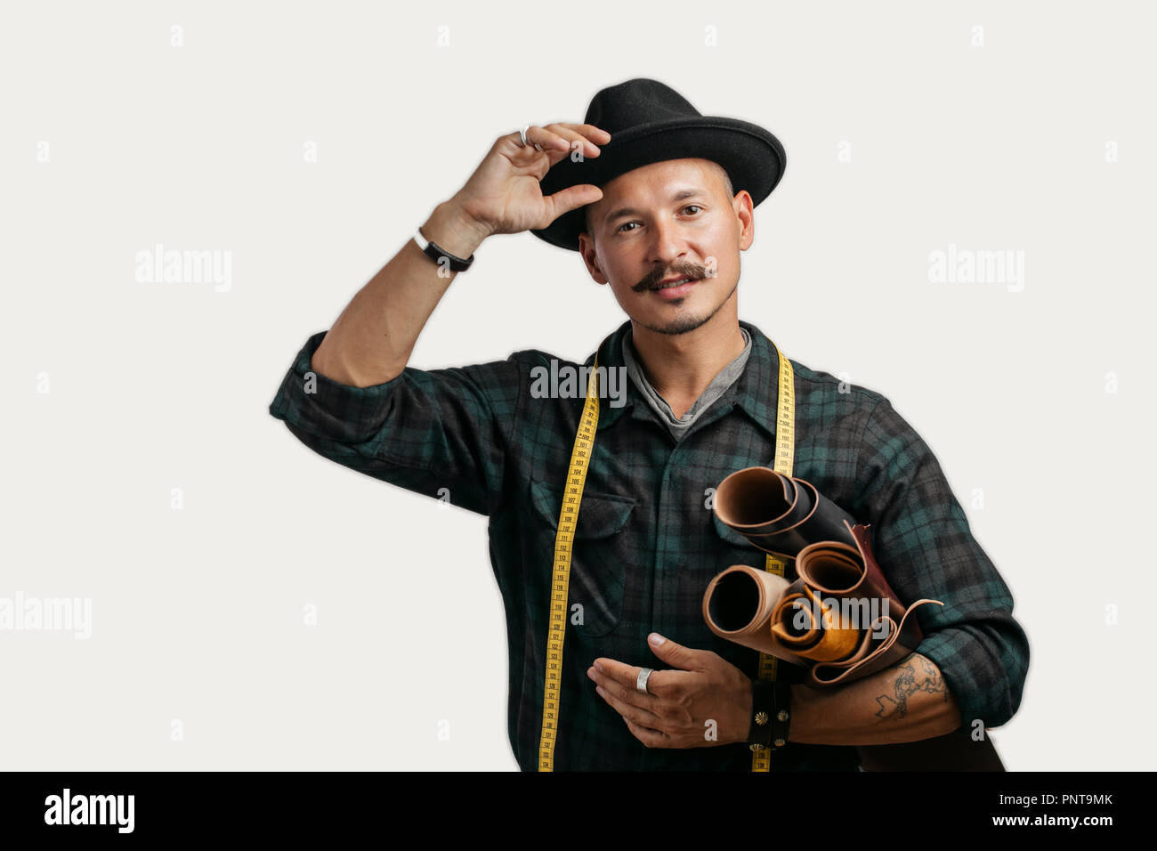 Artisan of leather in creative black hat posing with leather goods in studio. - Stock Image