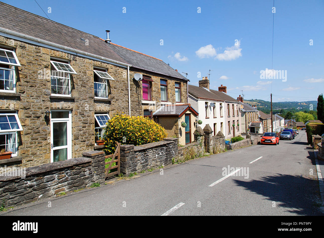 Swansea, UK: July 07, 2018: Street view of typical double fronted terraced house in a Welsh village. Summertime with garden flowers and blue sky. Stock Photo