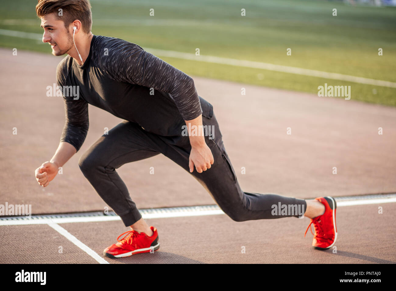 athlete in black clothes starting sprint on running track - Stock Image