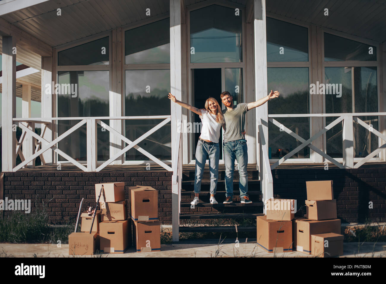 Husband and wife standing in front of new buying home with boxes - Stock Image