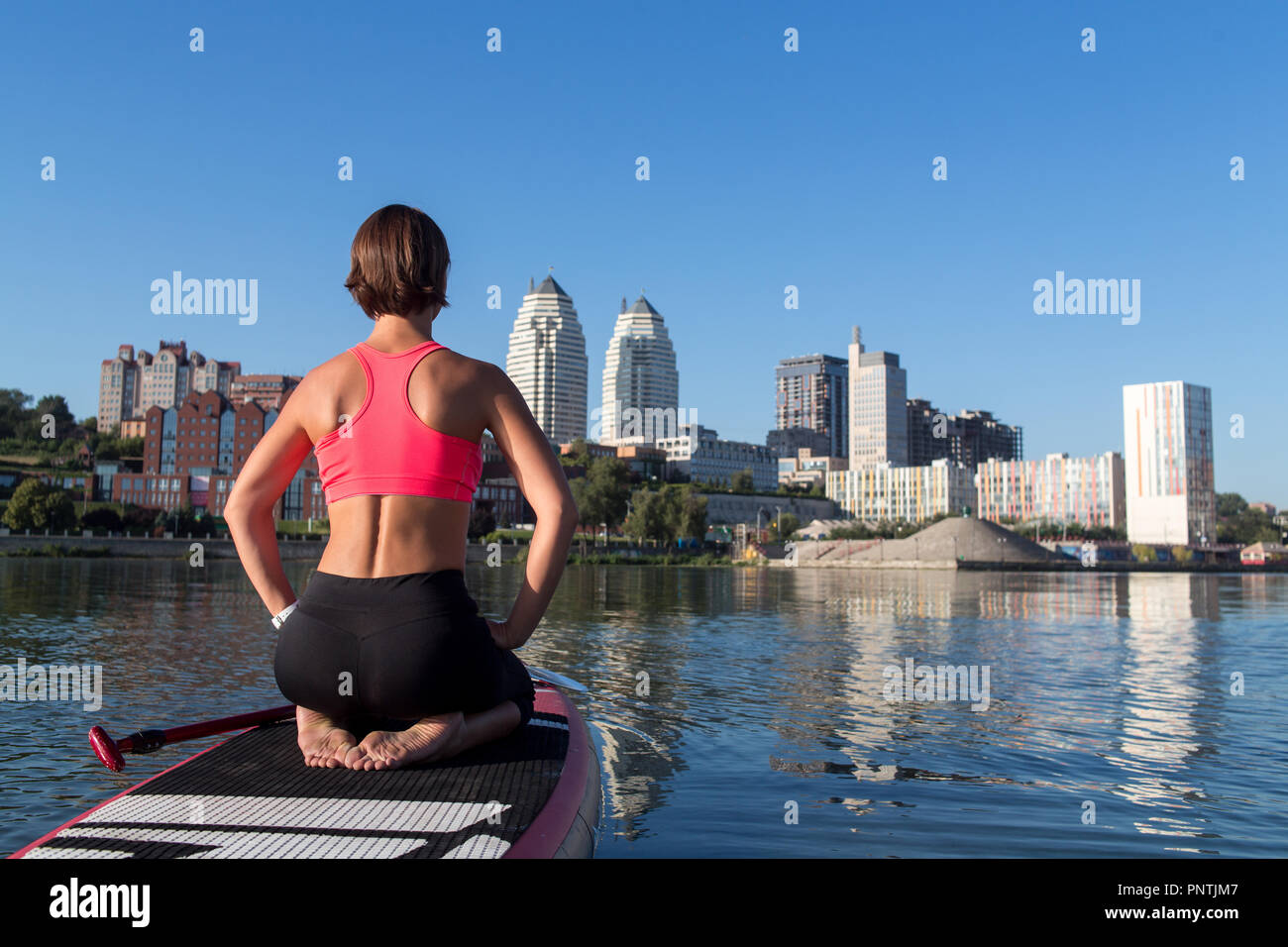 Woman practicing sitting variation of yoga pose on paddle board Stock Photo