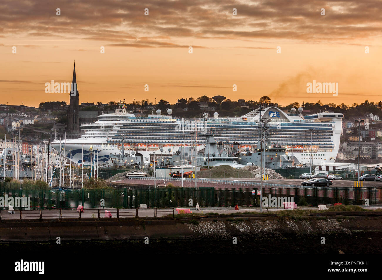 Cobh, Cork, Ireland. 22nd April, 2017.  Cruise liner Caribbean Princess passing  the Houlbowline Naval Base at dawn prior to her final turning manoeuv - Stock Image
