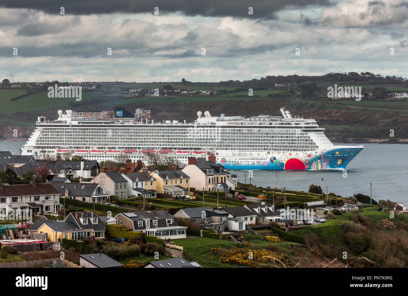 Church Bay, Cork, Ireland. 24th April, 2018. Cruise Liner Norwegian Breakaway steams out of the harbour, passing  homes in Church Bay after her visit  - Stock Image