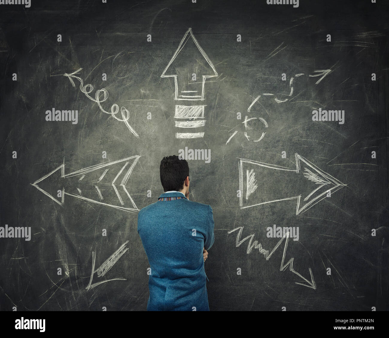 Rear view of pensive businessman thinking in front of a huge blackboard with arrows pointed to different directions. Difficult choice, decide which wa - Stock Image