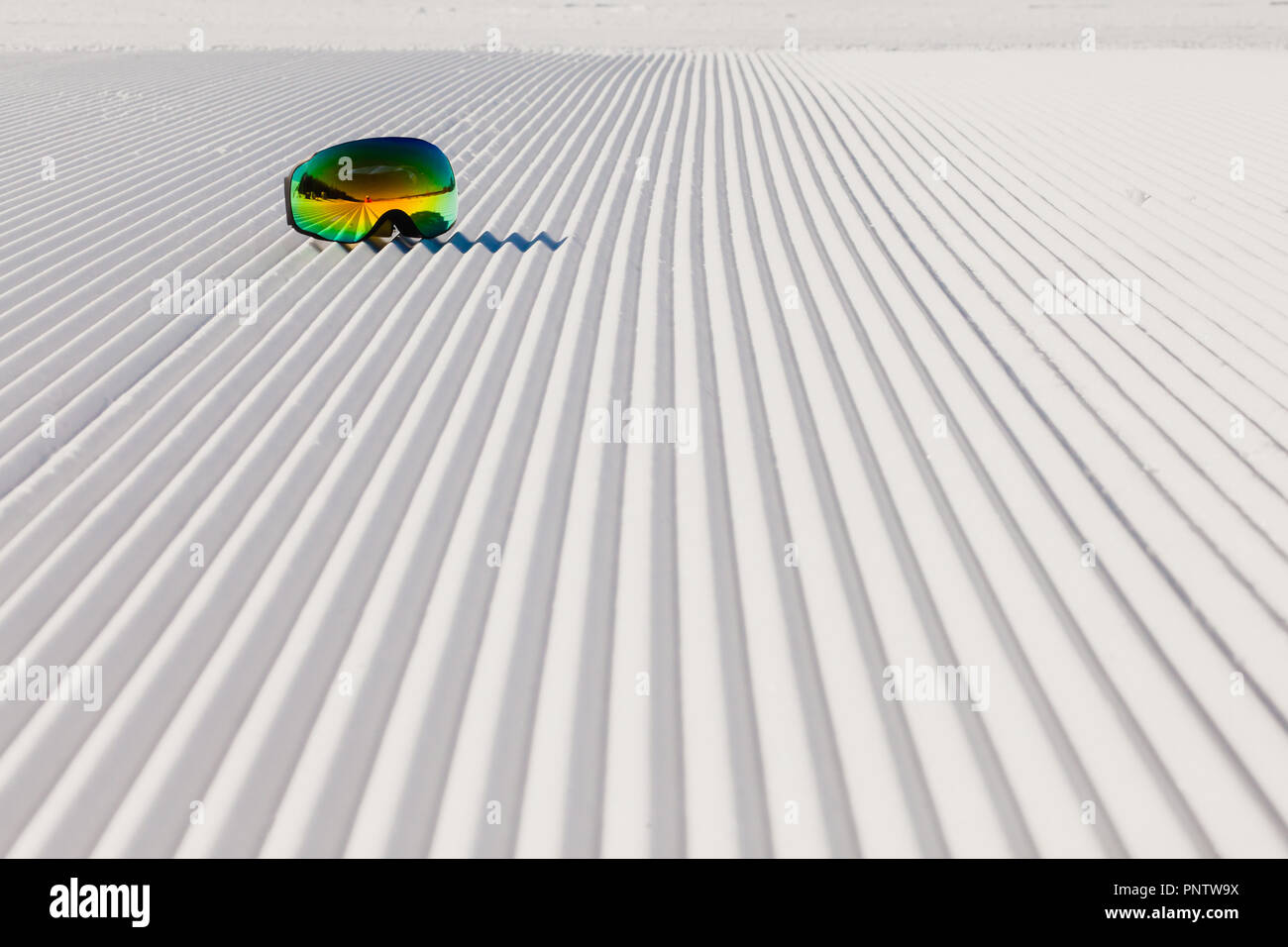 Close-up view of new groomed snow on empty ski slope and ski goggles on it - Stock Image