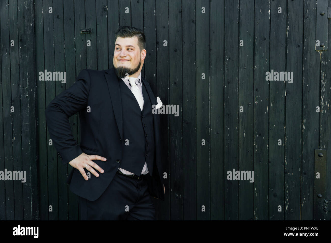 Bridegroom is standing in front of a wooden wall - Stock Image