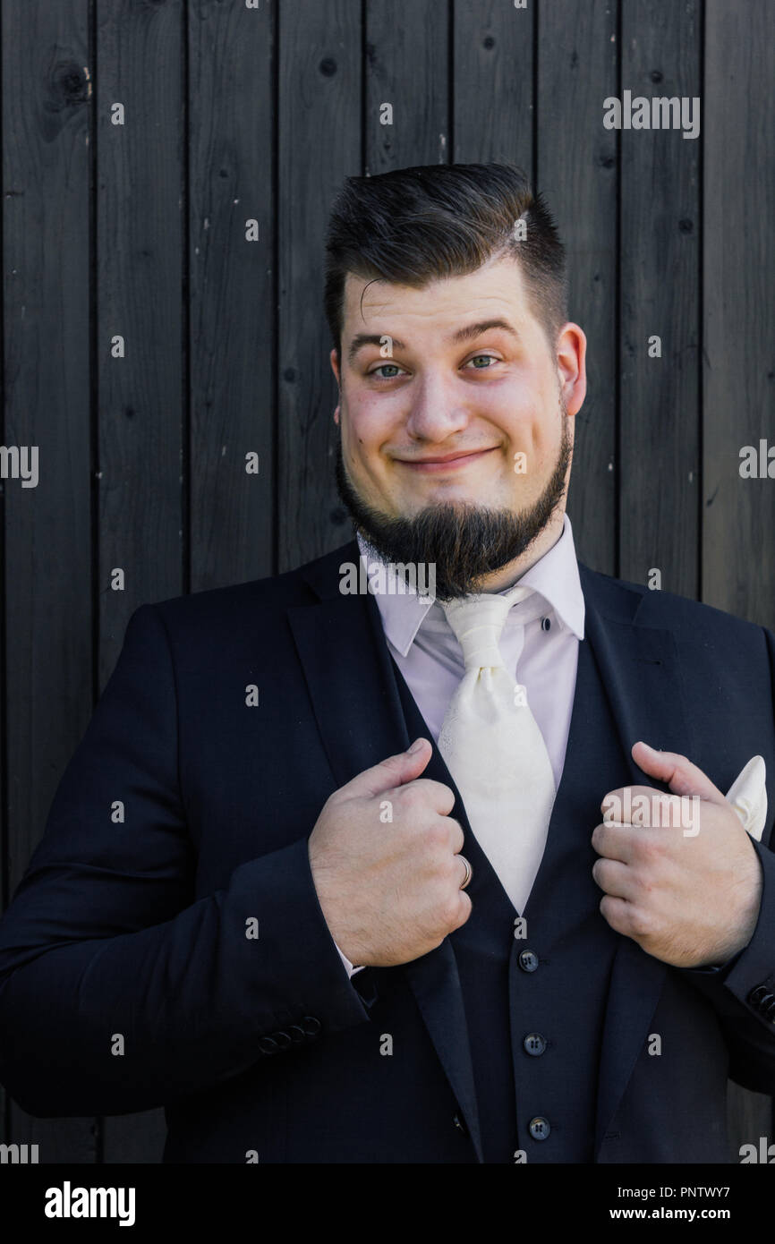 Bridegroom is standing in front of a wooden wall Stock Photo