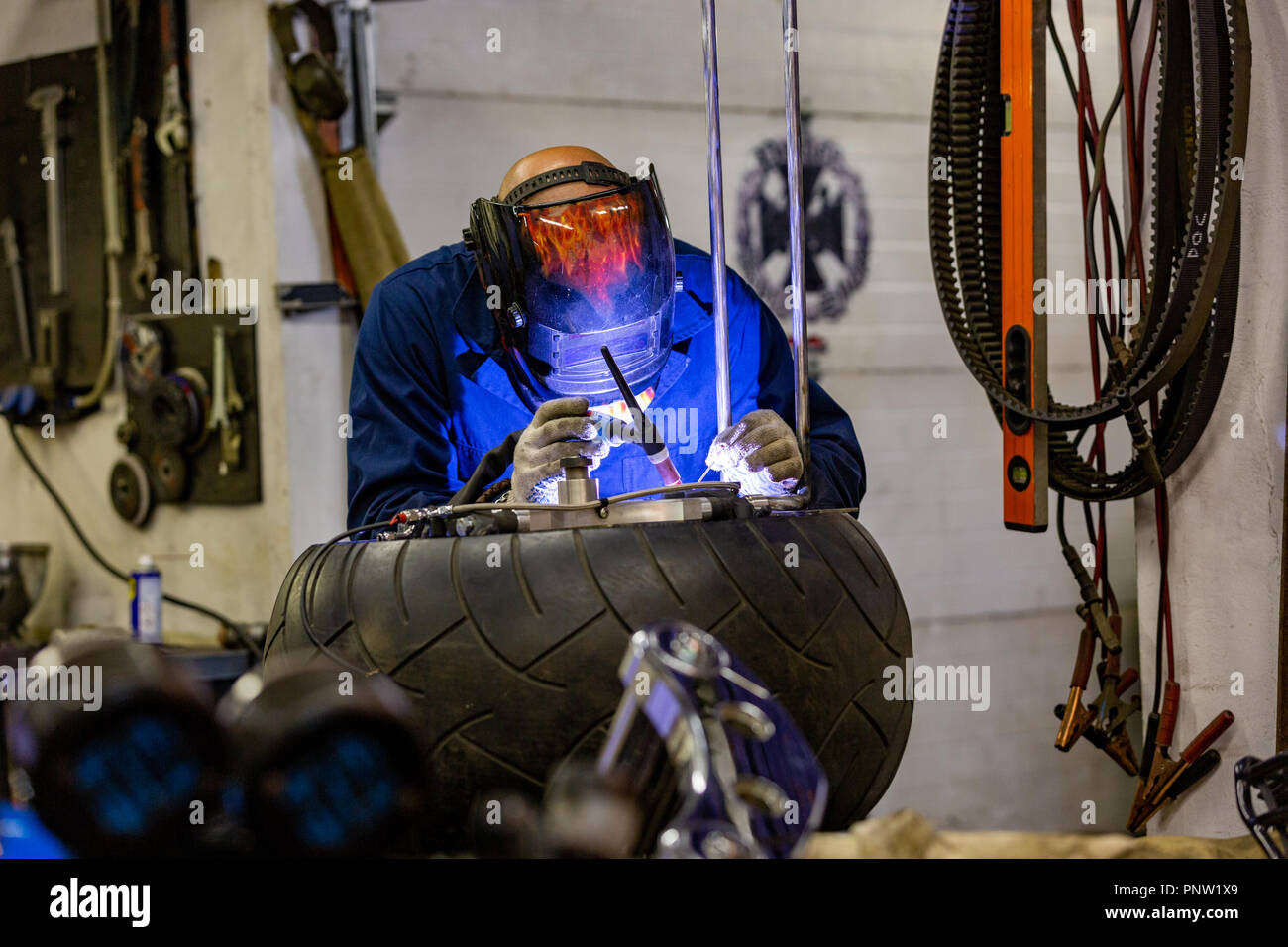 Professional car mechanic working in auto repair service on argon gas cutting machine - Stock Image